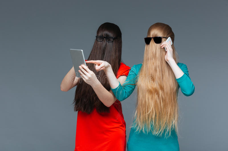 Two women with covered faces using mobile phone and tablet stock photos