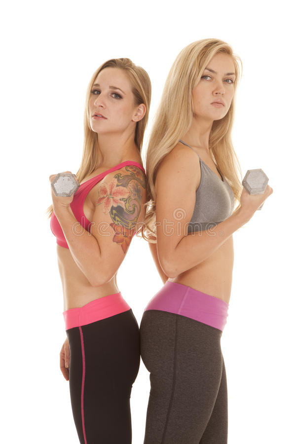Two women curl weights one tattoo both look stock photography