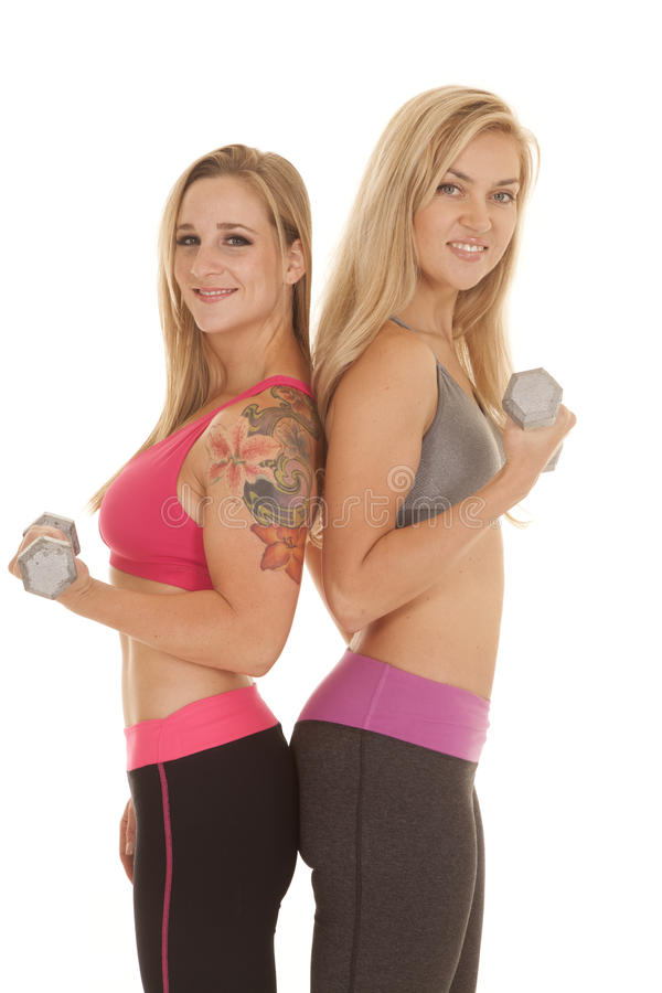Two women curl weights one tattoo smile. stock images