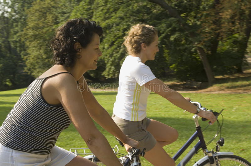Two women cycling. stock images