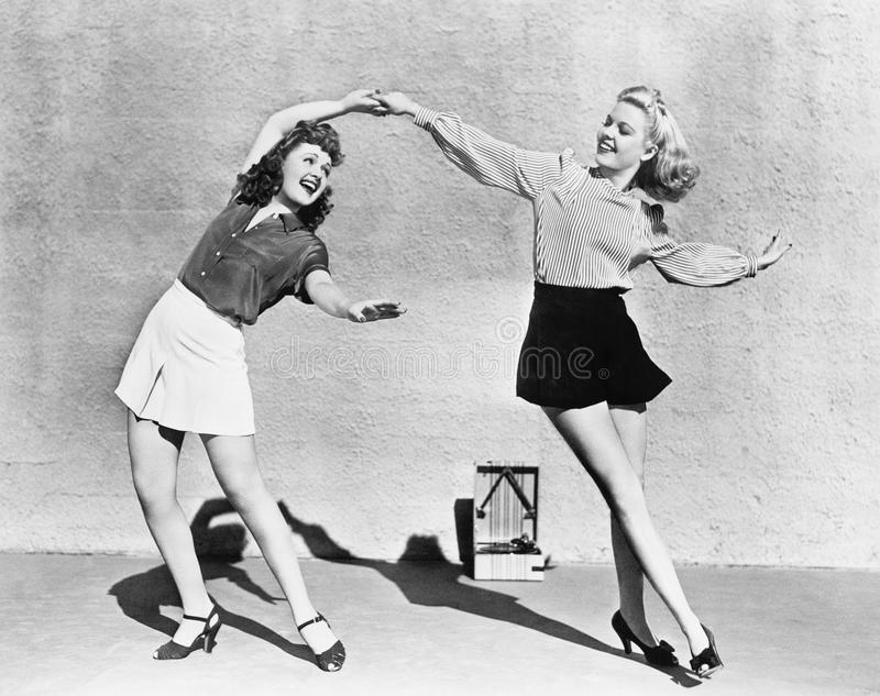 Two women dancing outside. (All persons depicted are no longer living and no estate exists. Supplier grants that there will be no model release issues stock photography