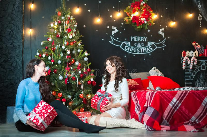 Two women in decorated room for Christmas laugh, see the gifts, have fun. Girlfriends in the room are preparing for the New Year royalty free stock images