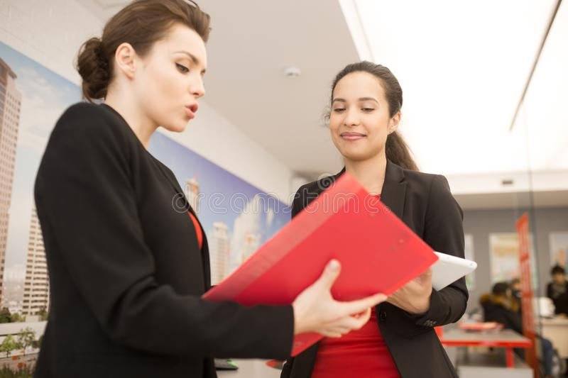 Two Women Discussing Work in Office royalty free stock photography