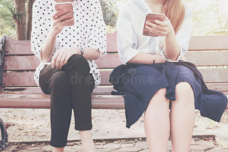 Two women in disinterest moment with smart phones in the outdoor, concept of relationship apathy and using new technology and smar stock photo