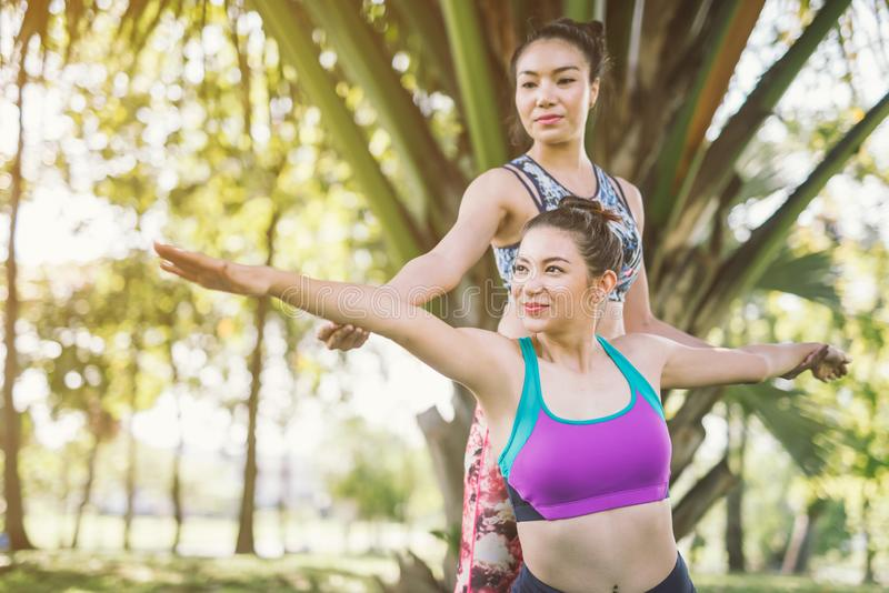 Two woman do yoga with friend. stock photo