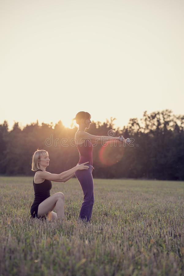 Two women doing exercises in a rural field royalty free stock image