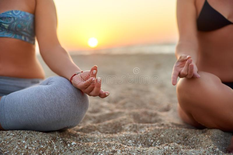 Two women doing group meditation on the beach on sunrise. Female friends doing yoga padmasana or lotus asana sitting on stock photos