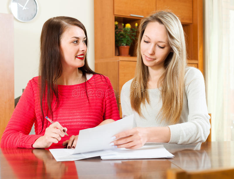 Two women doing office work. At the table royalty free stock image