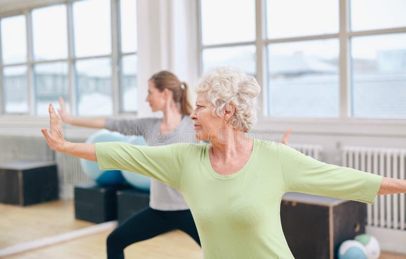 Two women doing yoga workout at gym stock photos
