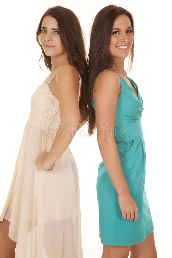 Two women dresses back to back. Two women are in dresses standing back to back royalty free stock images