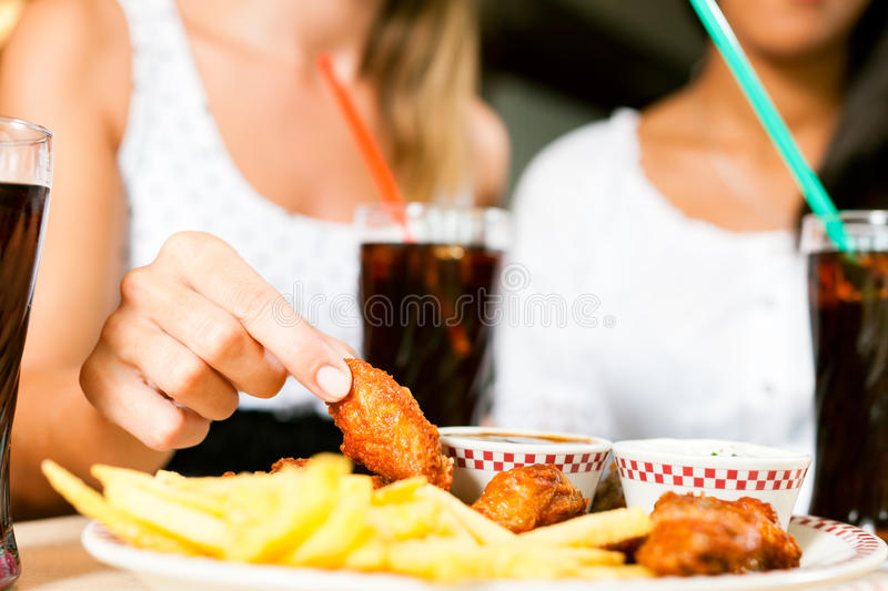 Two women eating chicken wings and drinking soda stock photo