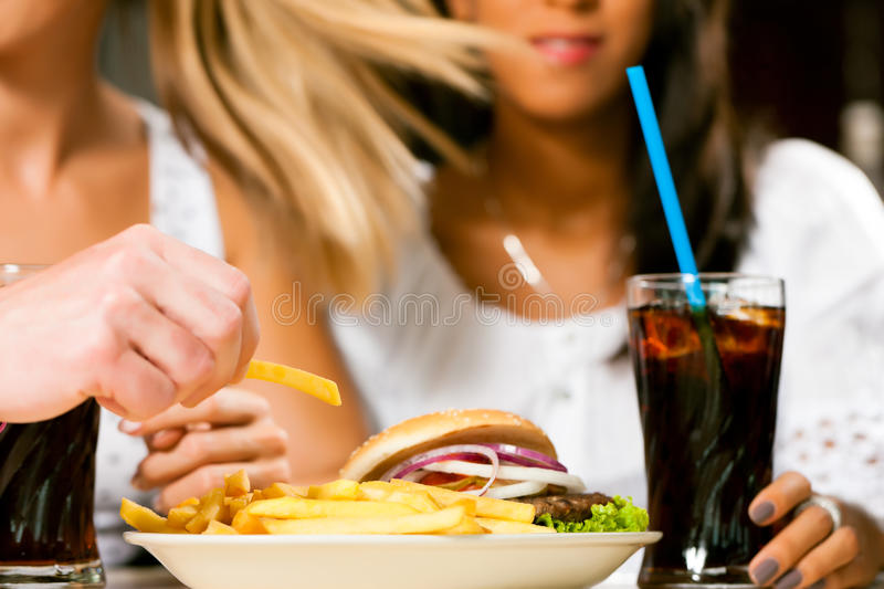 Two women eating hamburger and drinking soda. Two woman - one is African American - eating hamburger and drinking soda in a fast food diner; focus on the meal stock photography