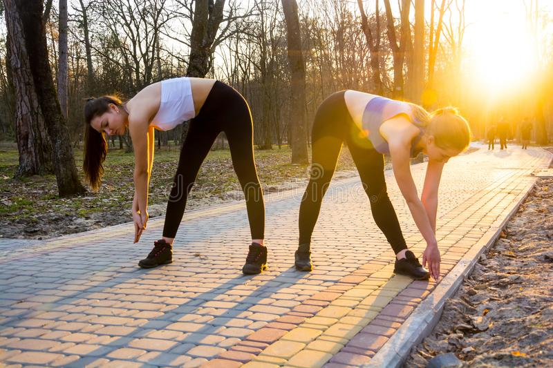 Two women are engaged in warm-up before running in the park in s. Two girls are engaged in warm-up before running in the park in sunlight stock photo