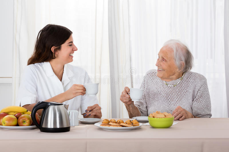 Two Women Enjoying Tea And Cookies royalty free stock image