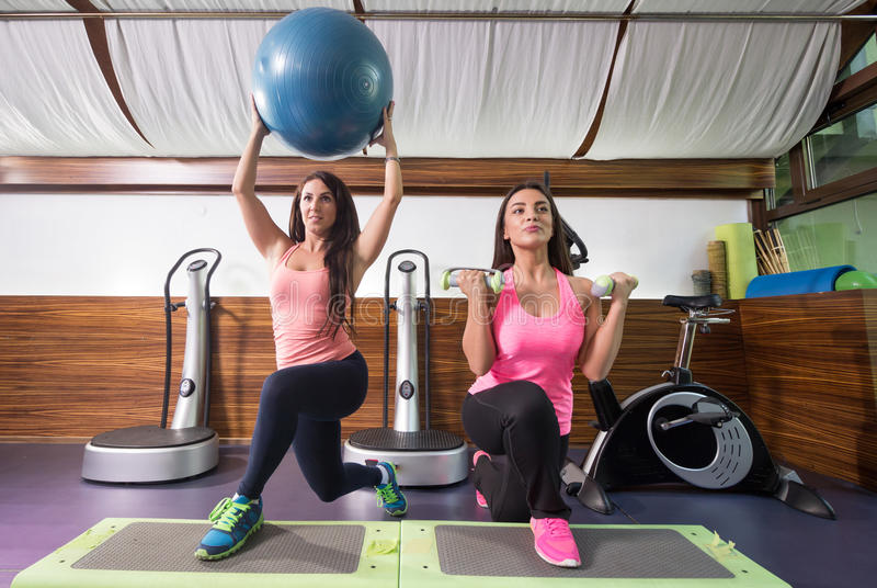 Two women exercise weights stability ball one leg lunge stepper stock images