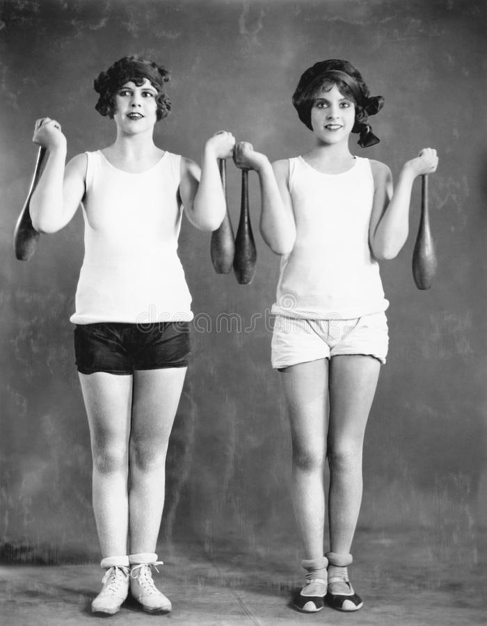 Two women exercising with juggling pins royalty free stock images