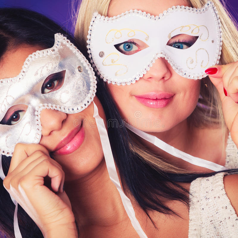 Two women face with carnival venetian masks stock photo