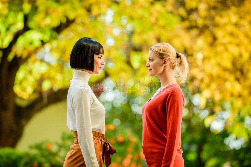 Two women are facing each other. girls looking into each others eyes. female friendship. walking in sunny park. best stock photography