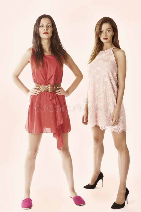 Two women. In fashion dresses, vertical full length standing portrait stock photos