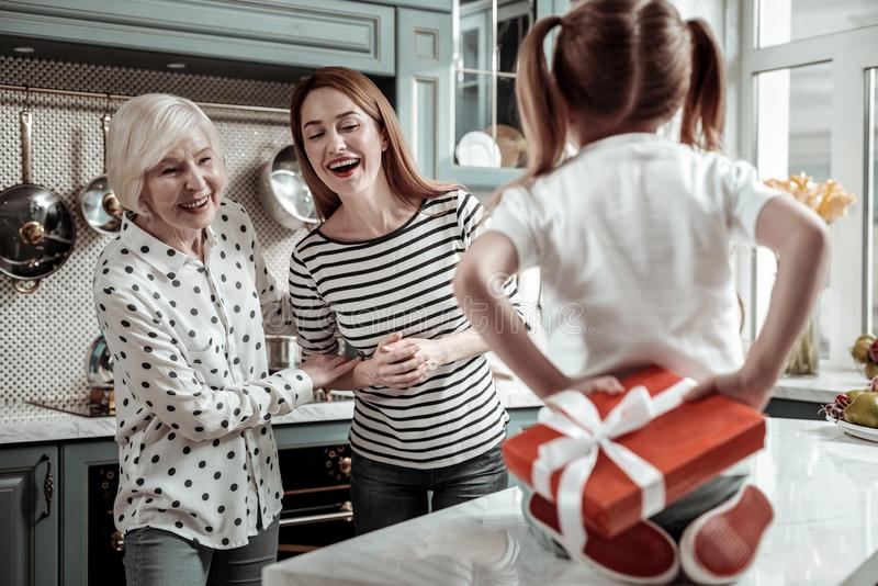 Two women feeling excited while little girl hiding her present royalty free stock photo