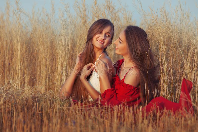 Two women in a field. Smiling two women are sitting in the field stock photography