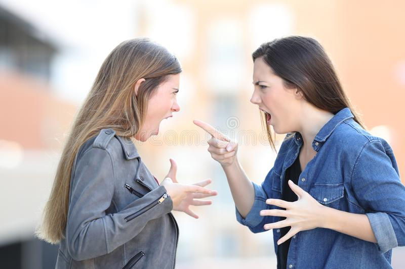Two women fighting shouting each other in the street royalty free stock photo