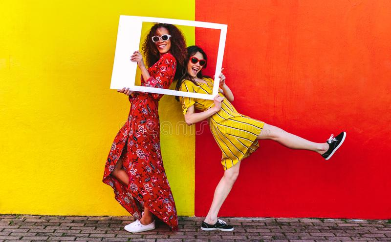 Girls posing with empty picture frame royalty free stock image