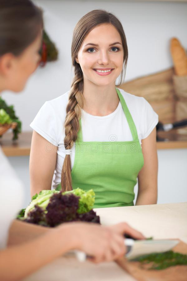 Two women friends cooking in kitchen while having a pleasure talk. Friendship and Chef Cook concept stock photos