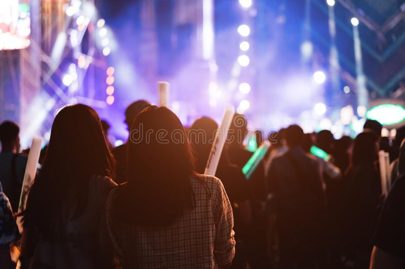 Two women friends crowd concert stage lights. And people fan audience silhouette raising hands glow stick in the music festival rear view with spotlight glowing stock photography
