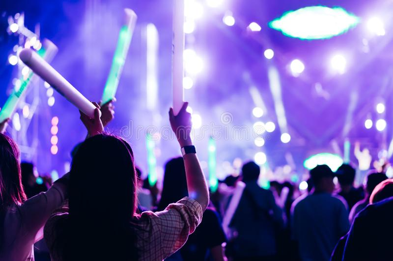 Two women friends crowd concert stage lights. And people fan audience silhouette raising hands glow stick in the music festival rear view with spotlight glowing royalty free stock images