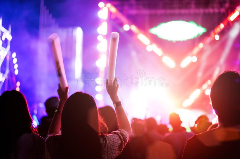 Two women friends crowd concert stage lights. And people fan audience silhouette raising hands glow stick in the music festival rear view with spotlight glowing stock photos