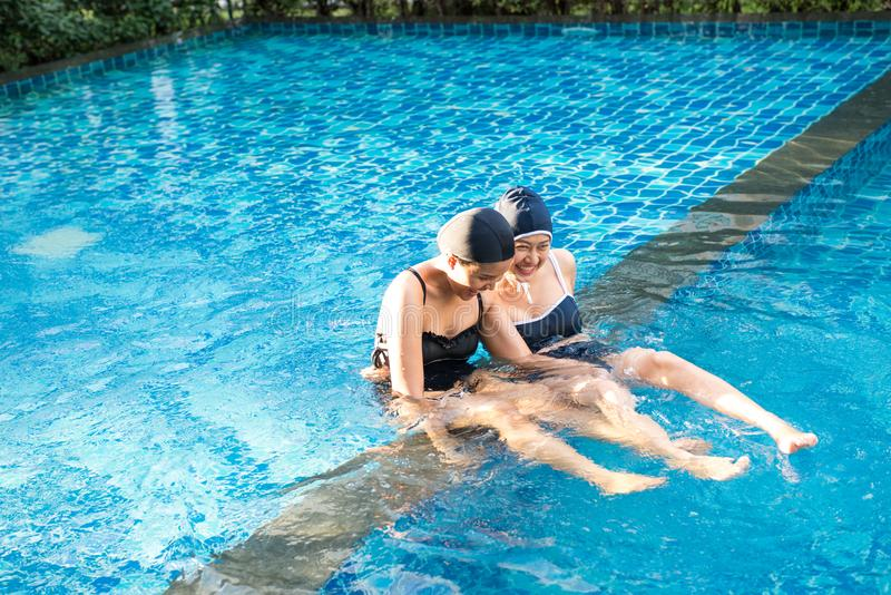 Two women friends having fun together in pool stock images