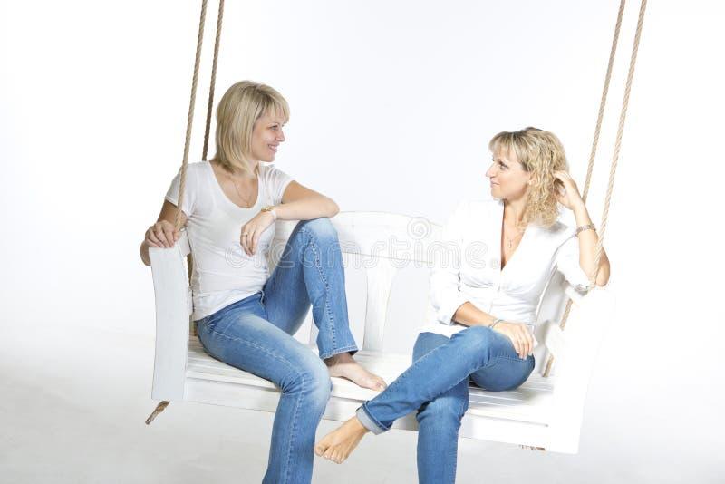Two women friends on a swing royalty free stock photo