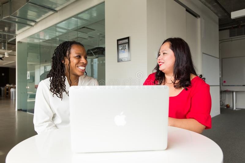 Two Women in Front of Silver Macbook royalty free stock photo