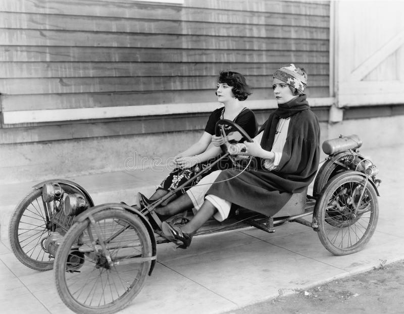 Two women in go kart. (All persons depicted are no longer living and no estate exists. Supplier grants that there will be no model release issues stock images