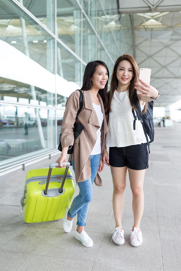Two women go travel and taking selfie in airport. Beautiful young asian woman stock photos