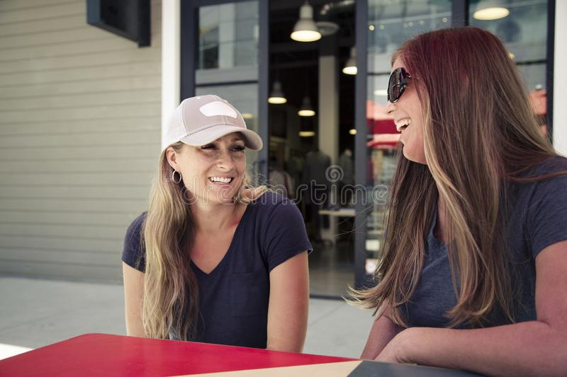Two women hanging out and talking at an outdoor cafe in a retail mail. Two women talking and smiling together as they sit at an outdoor cafe in a retail mall royalty free stock image