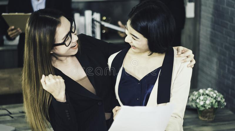 Two women happy and smiling happily with new job,with interview committee from Human Resources Department company standing behind. Desk,concept of starting new royalty free stock photography