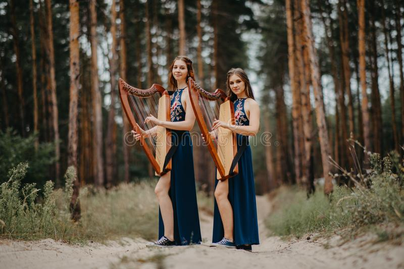 Two women harpists stand at forest and play harps against a background of pines. Two women harpists stand at forest and play harps in beautiful dresses against a royalty free stock photography
