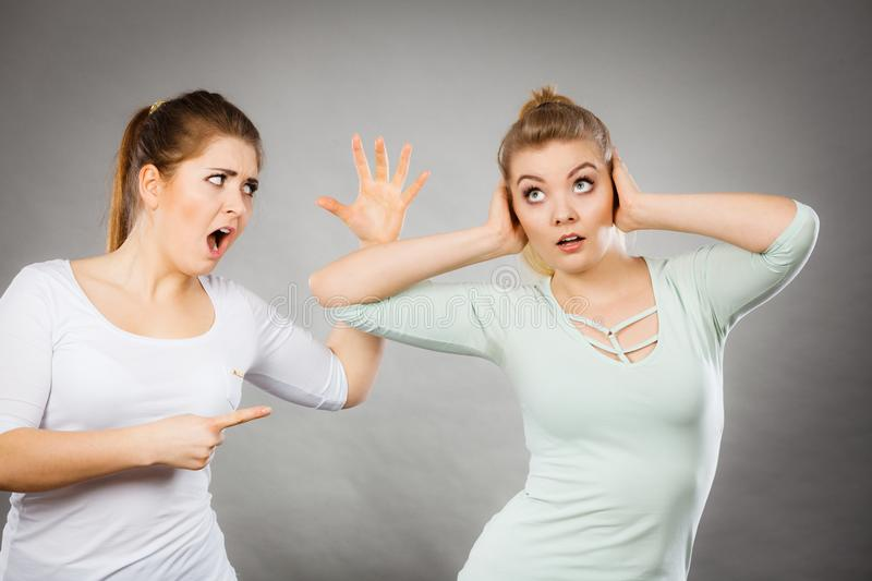 Two women having argue. Fight being mad at each other. Female telling off, ignorance concept stock image
