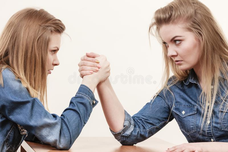 Two women having arm wrestling fight. Two serious competetive women having arm wrestling fight, compete with each other stock images