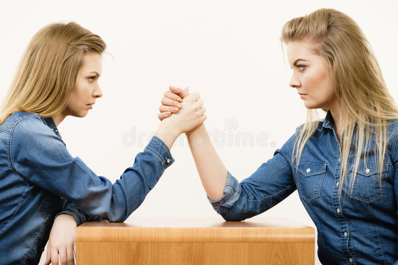 Two women having arm wrestling fight. Two serious competetive women having arm wrestling fight, compete with each other stock image