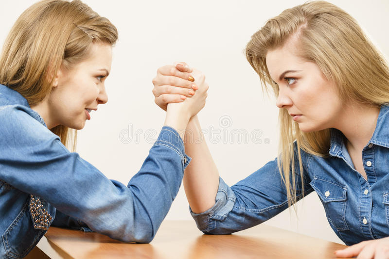 Two women having arm wrestling fight. Two serious competetive women having arm wrestling fight, compete with each other royalty free stock photo