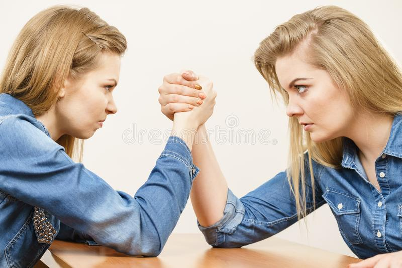 Two women having arm wrestling fight. Two serious competetive women having arm wrestling fight, compete with each other stock photos