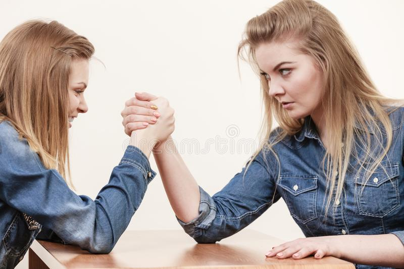 Two women having arm wrestling fight. Two serious competetive women having arm wrestling fight, compete with each other royalty free stock image