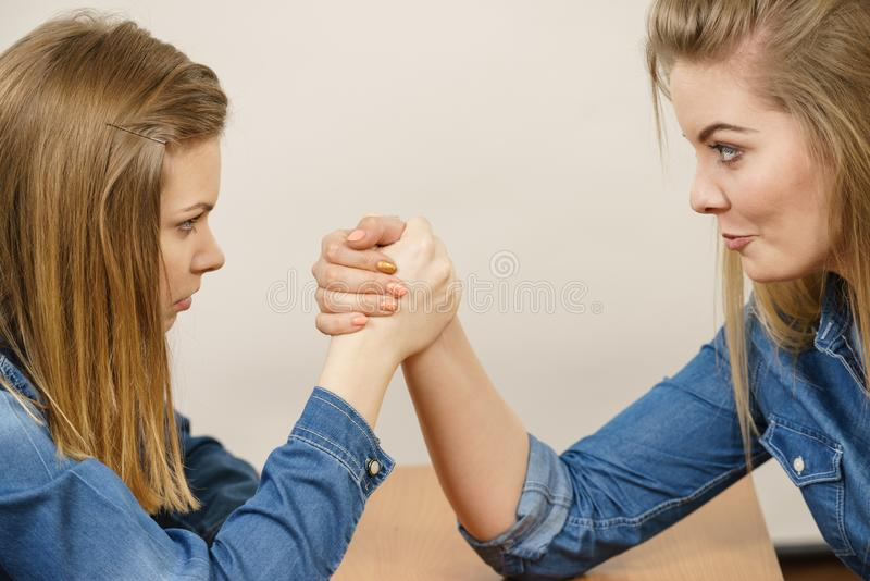 Two women having arm wrestling fight. Two serious competetive women having arm wrestling fight, compete with each other stock photography