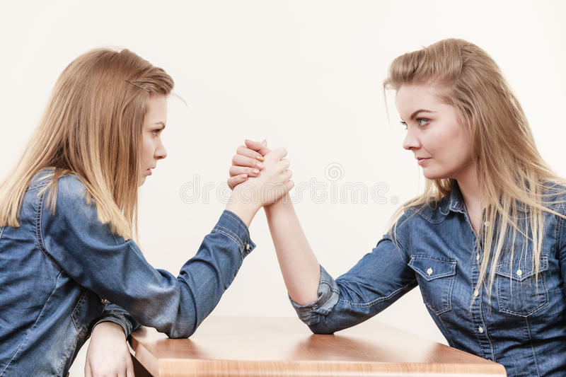Two women having arm wrestling fight. Two serious competetive women having arm wrestling fight, compete with each other royalty free stock photos