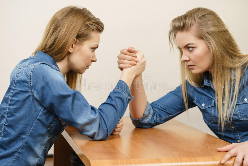 Two women having arm wrestling fight. Two serious competetive women having arm wrestling fight, compete with each other stock photo