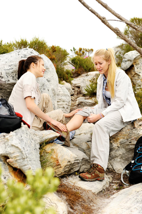 Two women help each other after one of them falls stock image