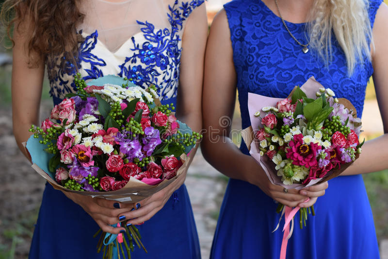 Two women holding bouquets. Two girls in blue dresses holding bouquets royalty free stock photos